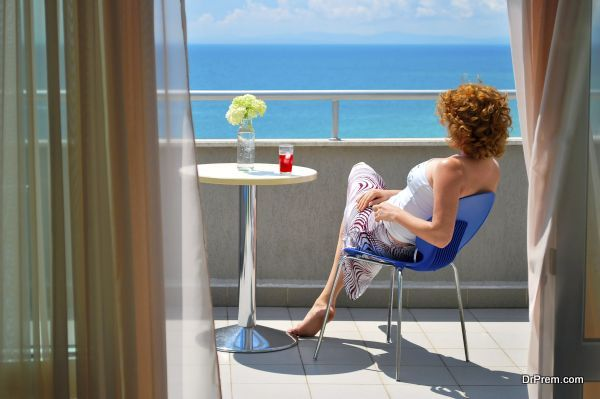 young woman sitting on the balcony at the see